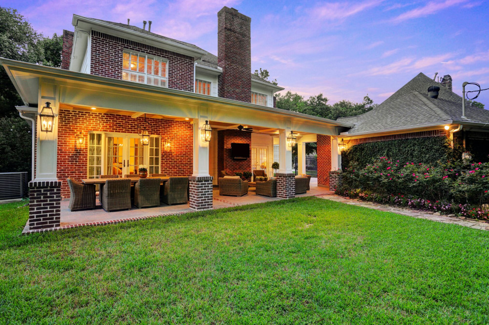 Inspiration for a mid-sized timeless backyard stamped concrete patio remodel in Houston with a roof extension