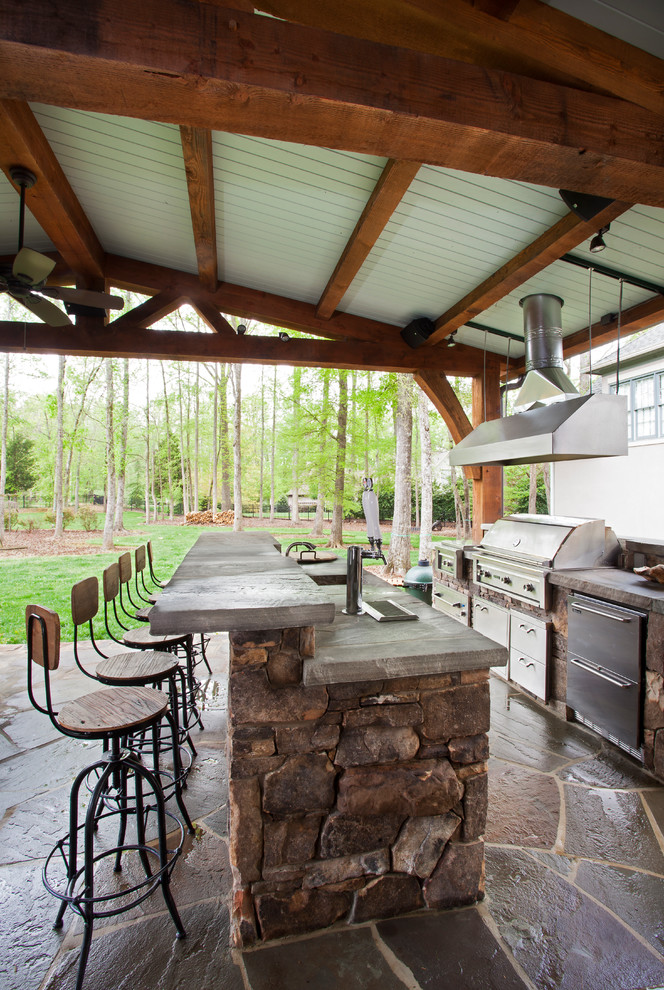 Patio kitchen - mid-sized traditional backyard stone patio kitchen idea in Charlotte with a roof extension