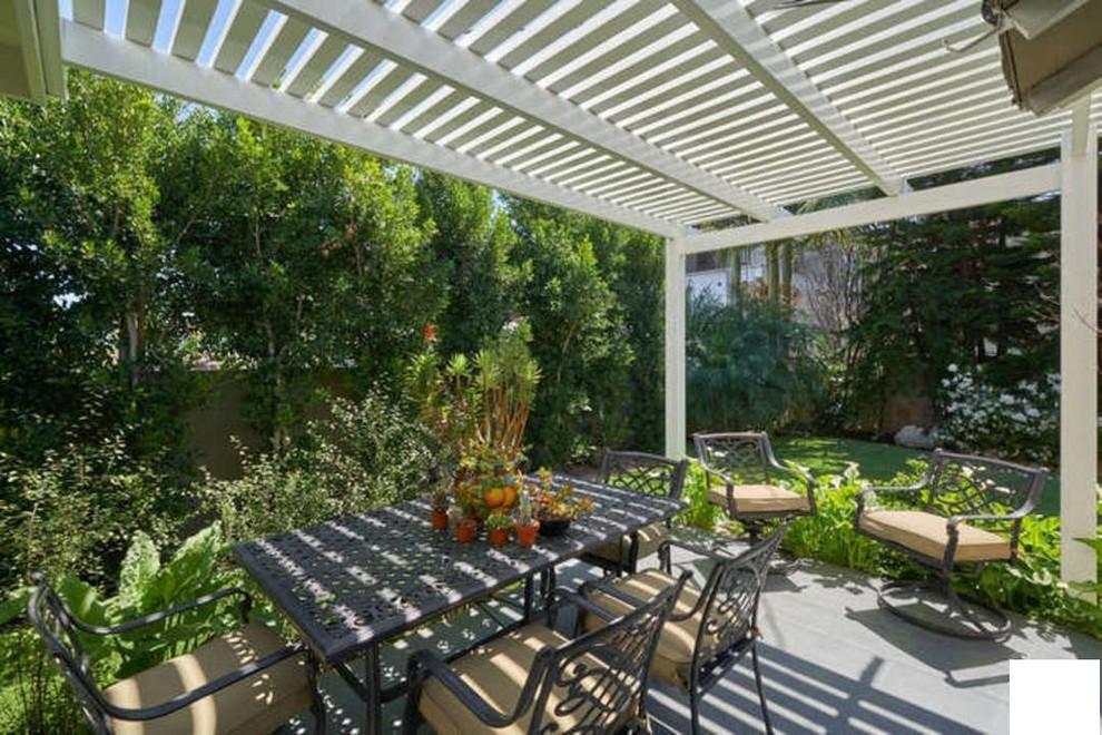 Ispirazione per un patio o portico mediterraneo di medie dimensioni e nel cortile laterale con un giardino in vaso, pavimentazioni in cemento e una pergola