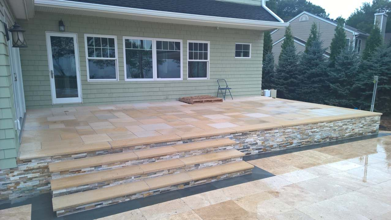 Raised patio using a natural tan stone with veneer on the face