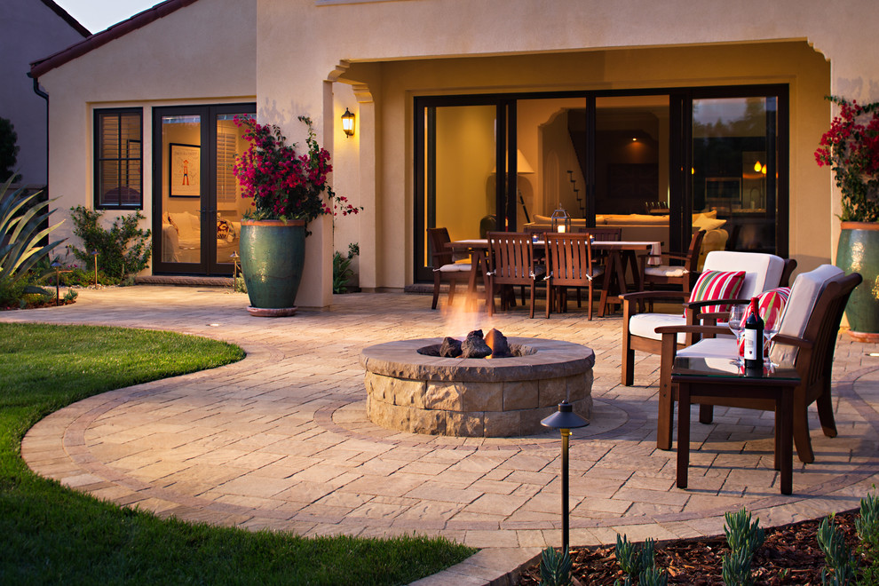 Inspiration for a mid-sized mediterranean backyard concrete paver patio remodel in San Diego with a fire pit and no cover