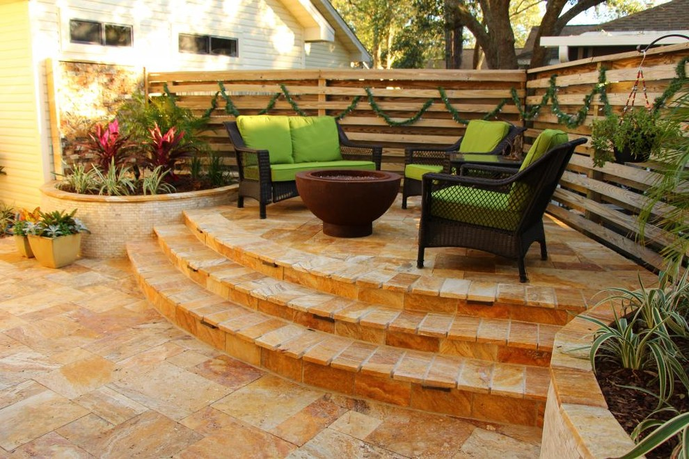 Example of a small island style backyard tile patio design in Miami with a fire pit