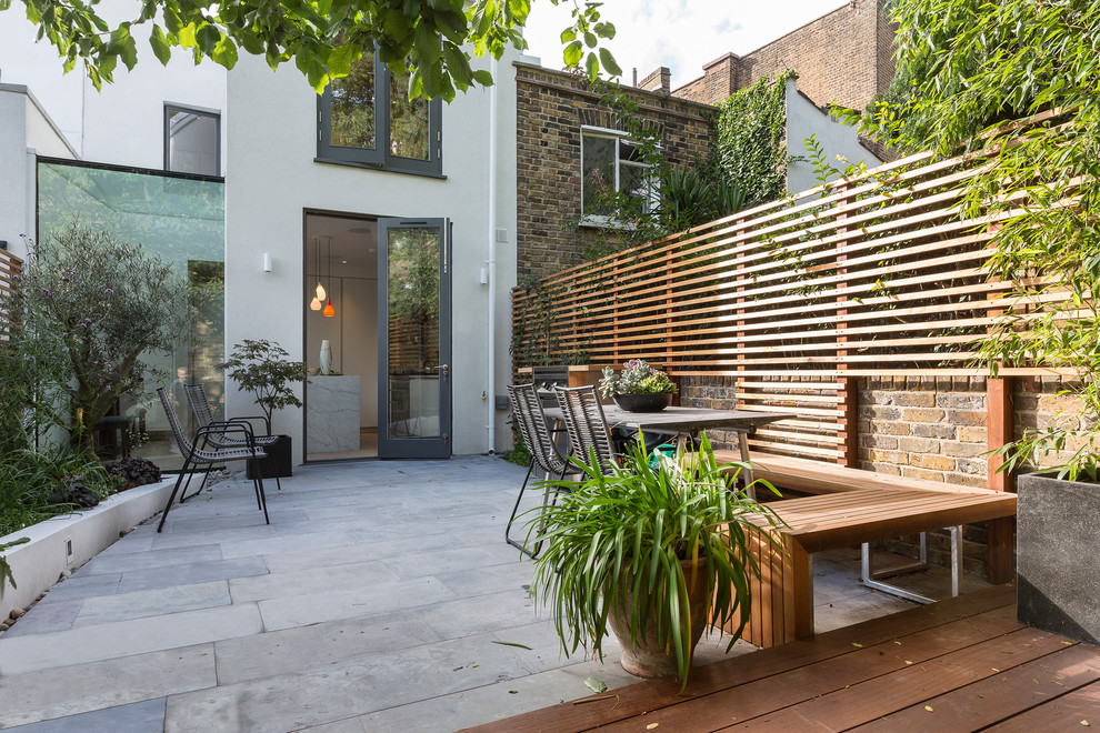 Mid-sized trendy backyard concrete paver patio photo in London with no cover