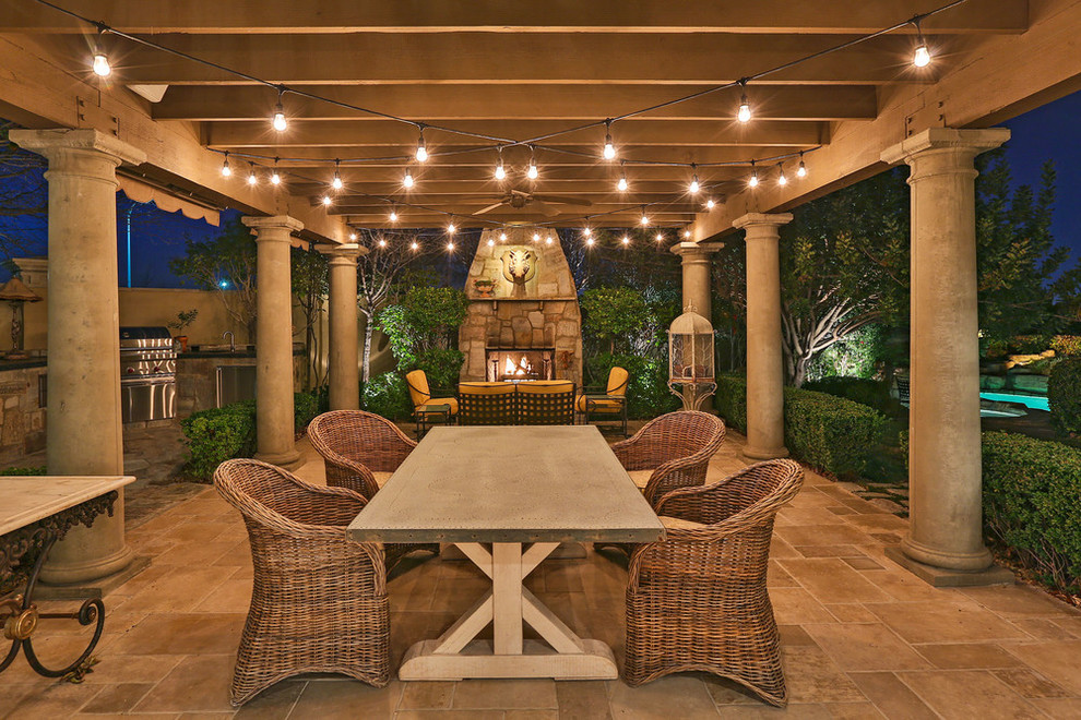 Example of an ornate tile patio design in Santa Barbara with a pergola