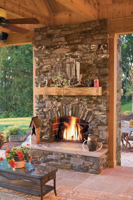 Inspiration for a rustic backyard stone patio remodel in San Diego with a fire pit and a roof extension
