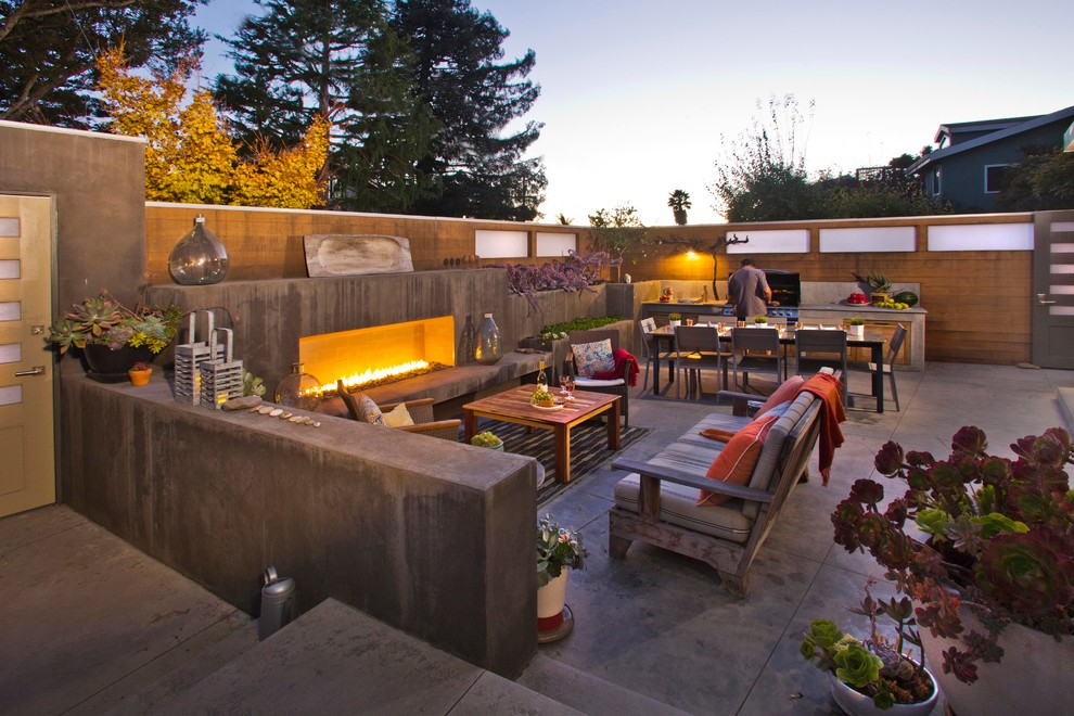 Inspiration for a contemporary backyard concrete patio remodel in San Francisco with no cover and a fireplace