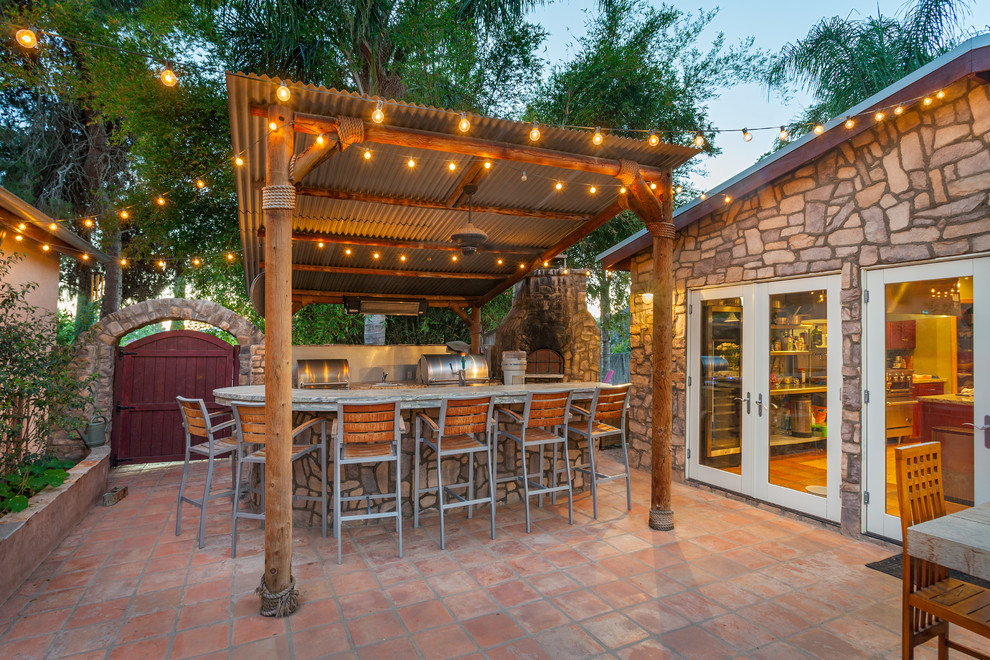 Mid-sized island style backyard tile patio kitchen photo in San Diego with a gazebo