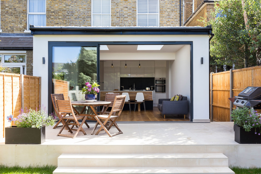 Example of a mid-sized trendy backyard tile patio design in London