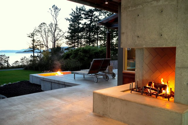 Outdoor fireplace and fire pit at dusk, with views towards Skagit Bay. modern patio