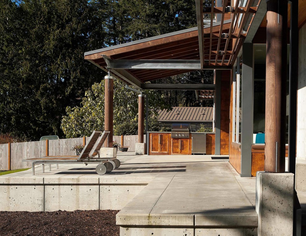 Patio kitchen - mid-sized modern front yard concrete patio kitchen idea in Seattle with a roof extension