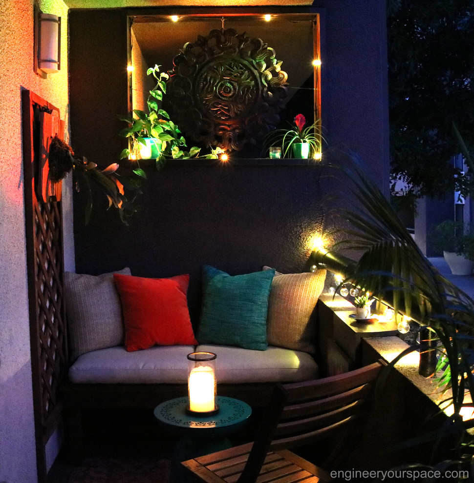 Patio - small tropical patio idea in Los Angeles with a roof extension