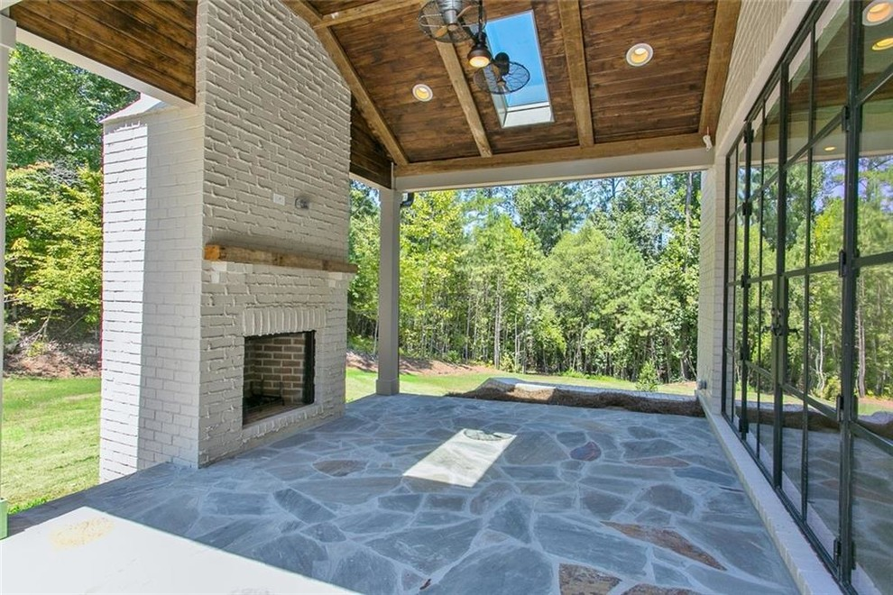 Example of a mid-sized cottage backyard stone patio design in Atlanta with a fireplace and a roof extension