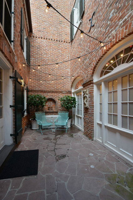 Patio - small traditional courtyard stone patio idea in New Orleans with no cover