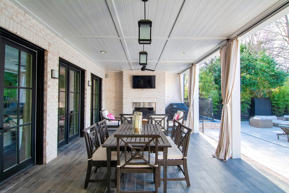 Inspiration for a transitional tile patio remodel in Charlotte with a fireplace and a roof extension