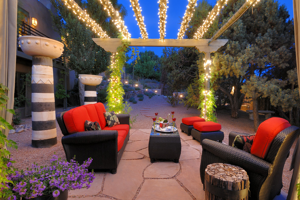 Mid-sized southwest backyard stone patio photo in Albuquerque with a pergola