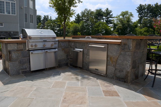 stone based outdoor kitchen with concrete countertops