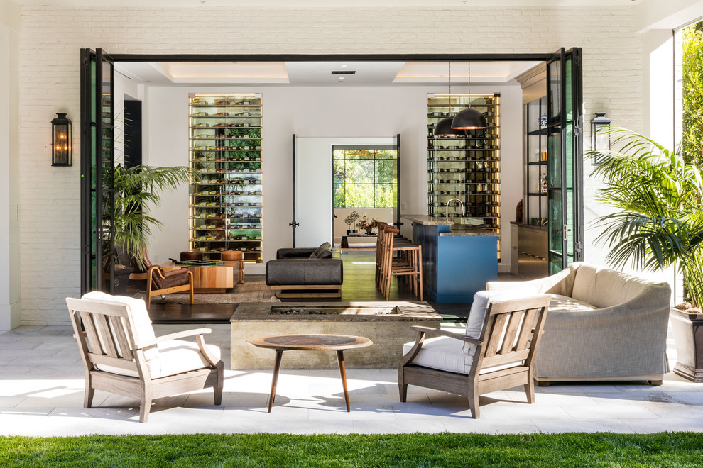 Inspiration for a large contemporary backyard stone patio remodel in Los Angeles with a roof extension