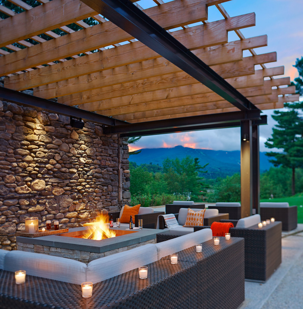 Example of a mid-sized trendy backyard patio design in Burlington with a fire pit and a pergola