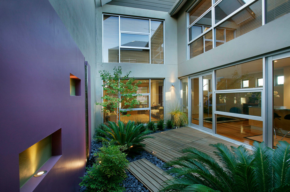 Inspiration for a small contemporary courtyard patio fountain remodel in Perth with decking