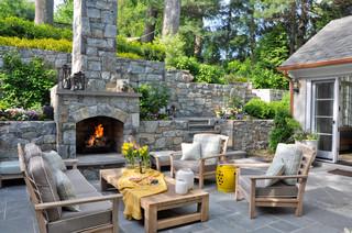 Outdoor fireplace built in hillside using natural rock.