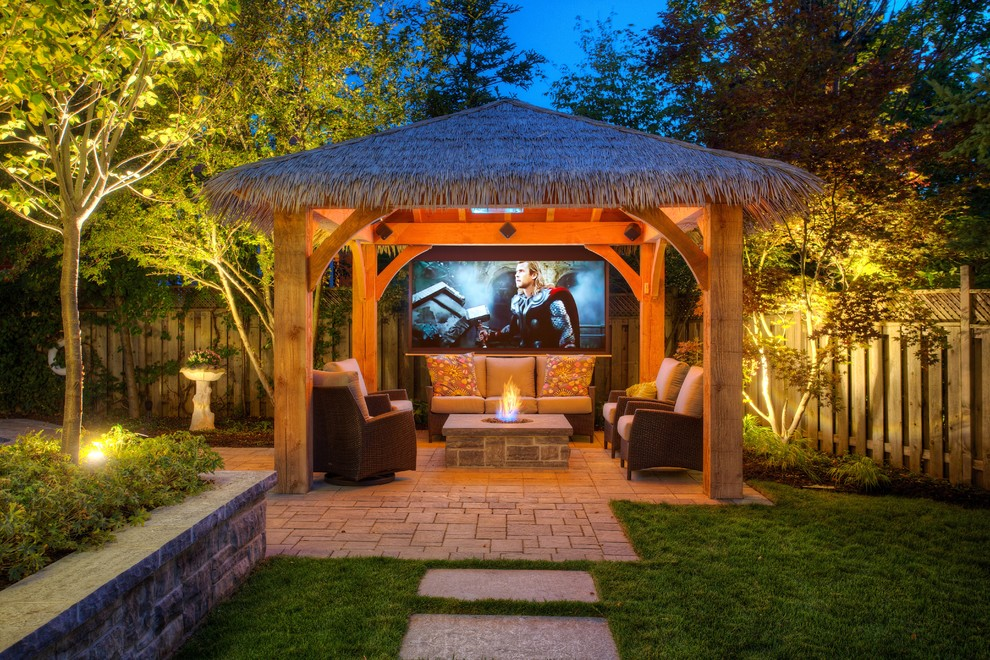 Example of an island style patio design in Toronto with a fire pit and a gazebo
