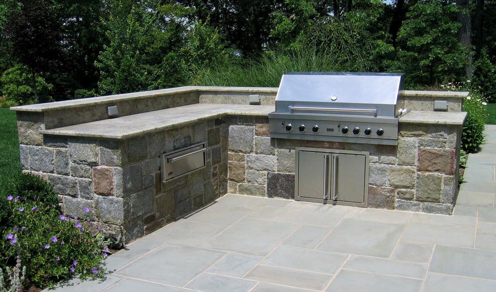 Modelo de patio clásico, sin cubierta, en patio trasero, con cocina exterior y adoquines de piedra natural