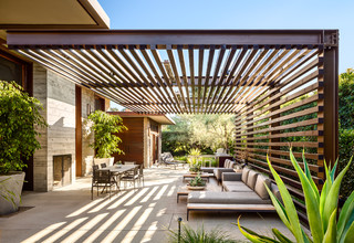Example Of A Trendy Concrete Patio Design In Santa Barbara With Pergola And Fireplace