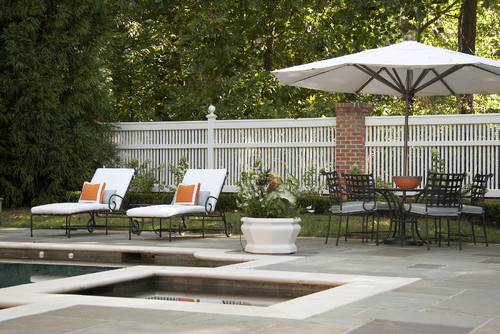 A tall vinyl pool fence surrounding a luxurious backyard patio and pool complex.