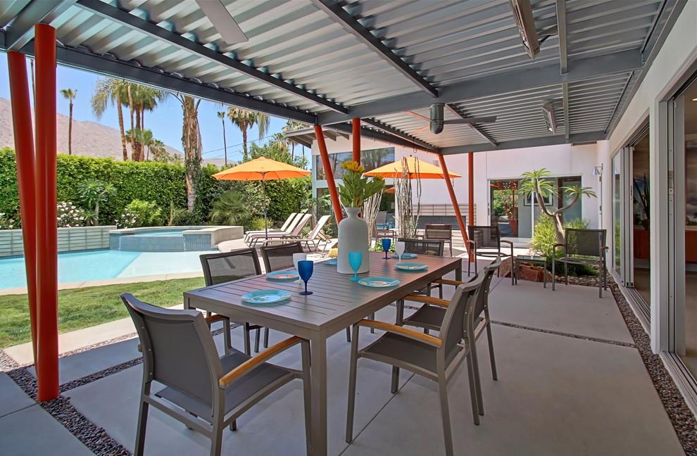Patio kitchen - large 1960s backyard concrete paver patio kitchen idea in Los Angeles with a pergola