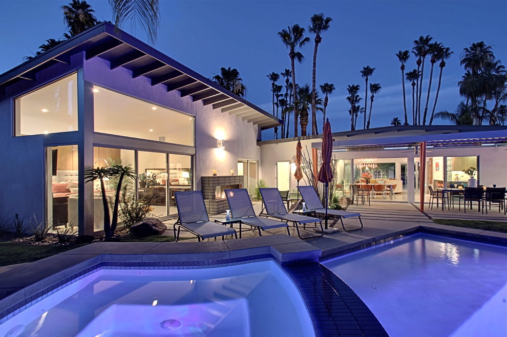 Large trendy backyard concrete paver patio photo in Los Angeles with an awning
