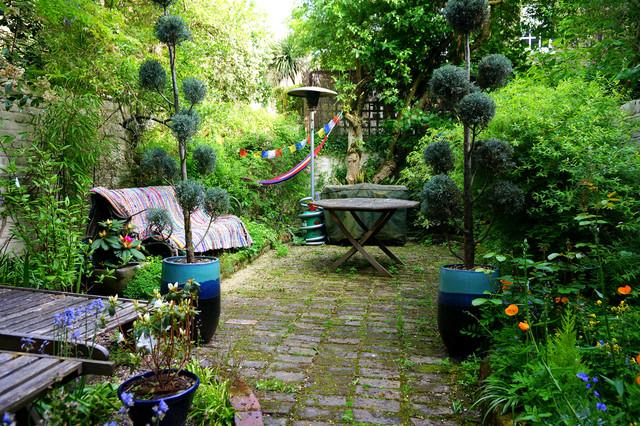 Modelo de patio bohemio, sin cubierta, en patio trasero, con adoquines de piedra natural
