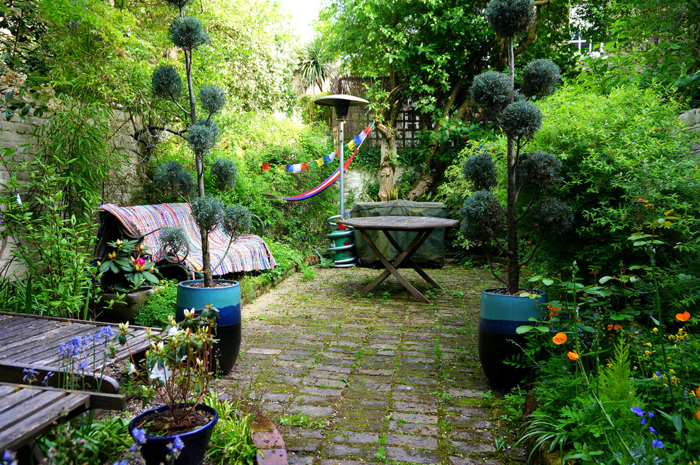 Example of an eclectic backyard stone patio design in London with no cover