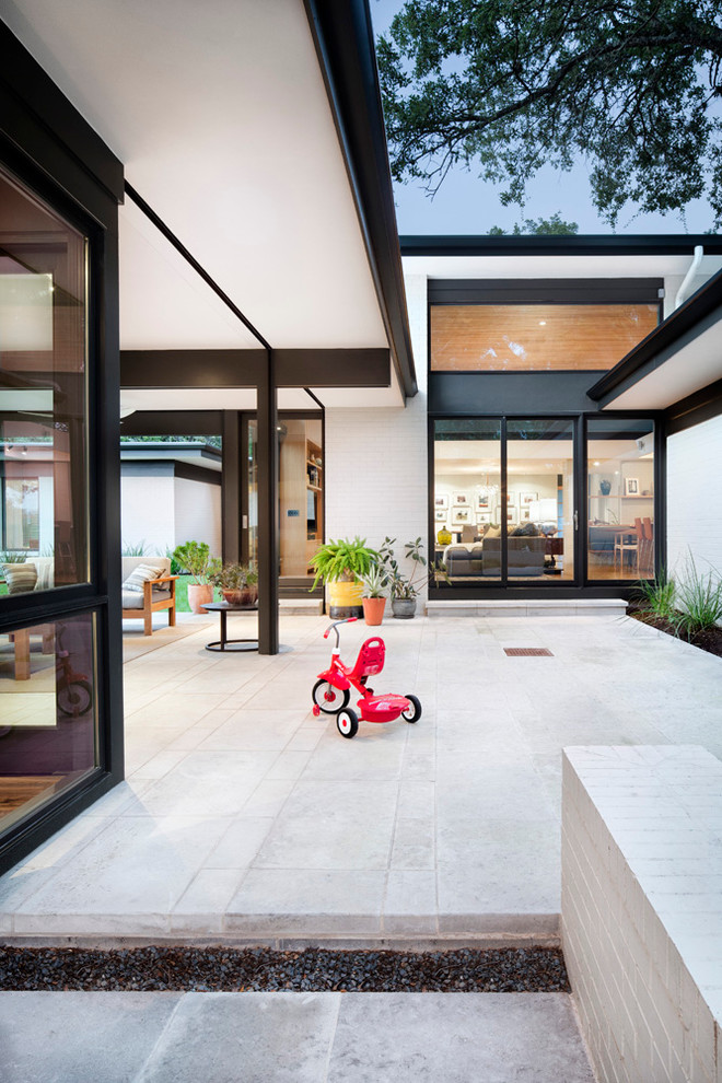 Patio container garden - mid-sized contemporary courtyard stone patio container garden idea in Austin with a roof extension