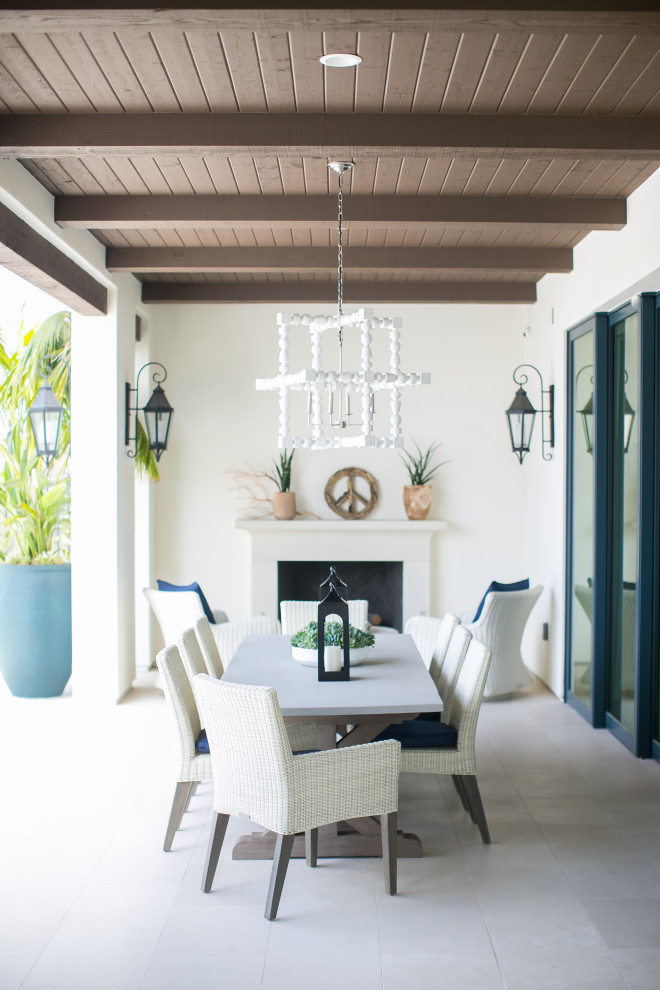 Example of a beach style patio design in Orange County with a fireplace and a roof extension