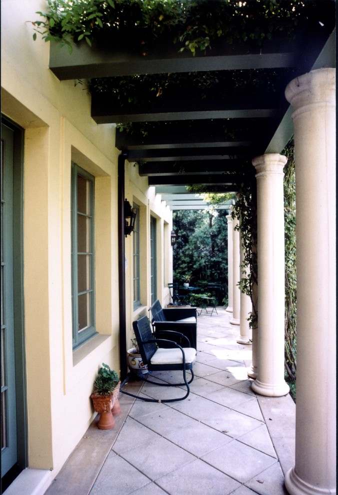 Inspiration for a large timeless backyard concrete patio remodel in Los Angeles with an awning