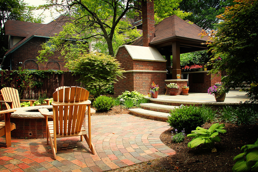 Inspiration for a timeless stone patio remodel in Cleveland with a fire pit and a gazebo