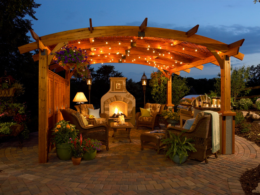 Patio - large traditional backyard stone patio idea in Other with a gazebo