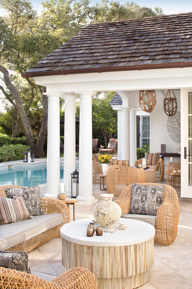 Large elegant backyard tile patio photo in Miami with a roof extension
