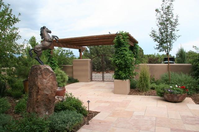Patio container garden - southwestern front yard stone patio container garden idea in Albuquerque with a pergola