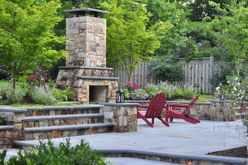 Large elegant backyard stone patio photo in DC Metro with a fire pit and no cover