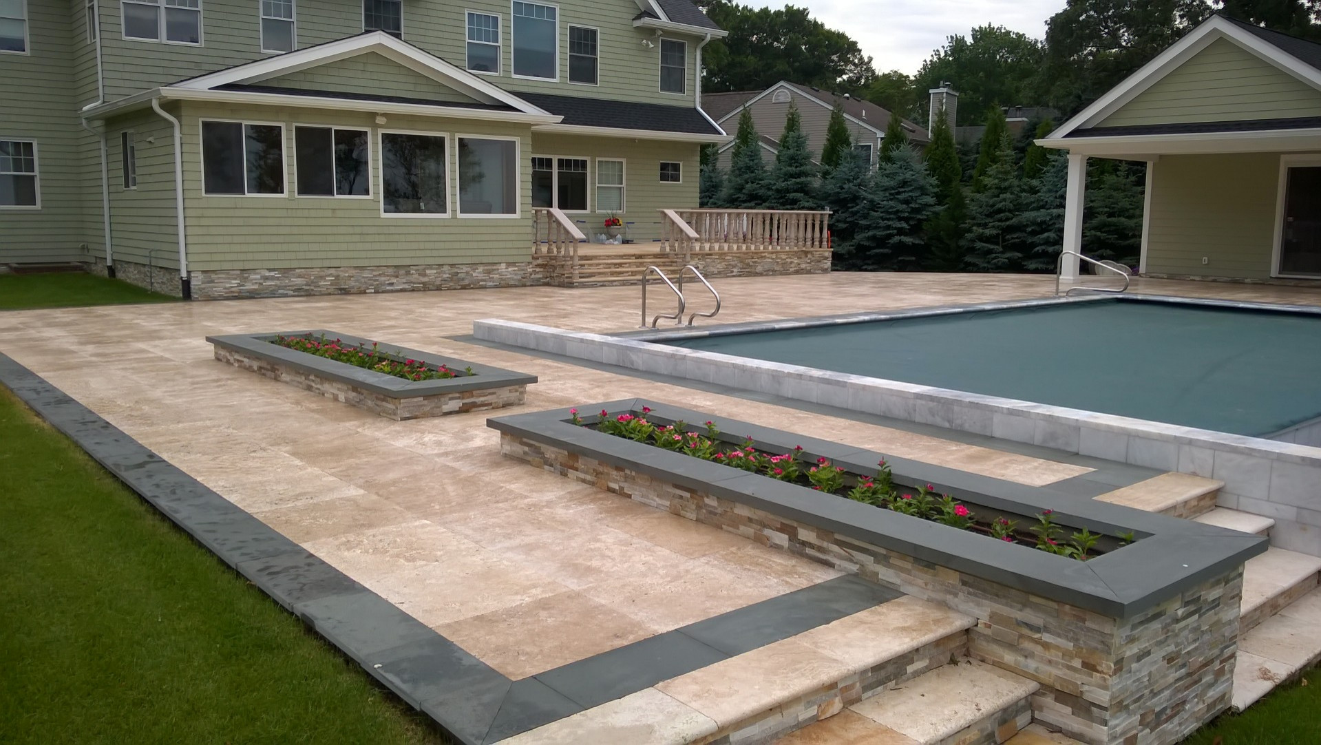 Travertine and bluestone patio with marble coping