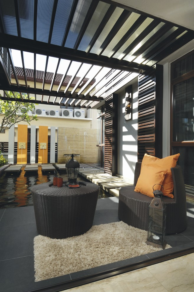 Inspiration for a tropical patio fountain remodel in Other with a pergola