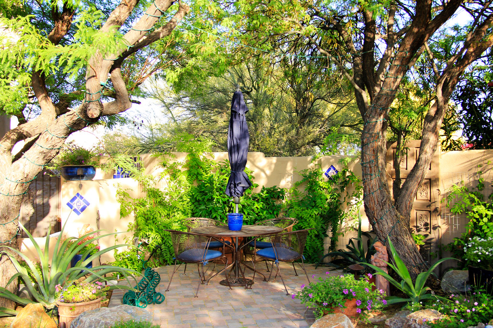 Inspiration for a mid-sized mediterranean backyard brick patio fountain remodel in Phoenix with no cover
