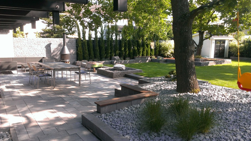 Large trendy patio photo in Frankfurt with a roof extension and a fireplace