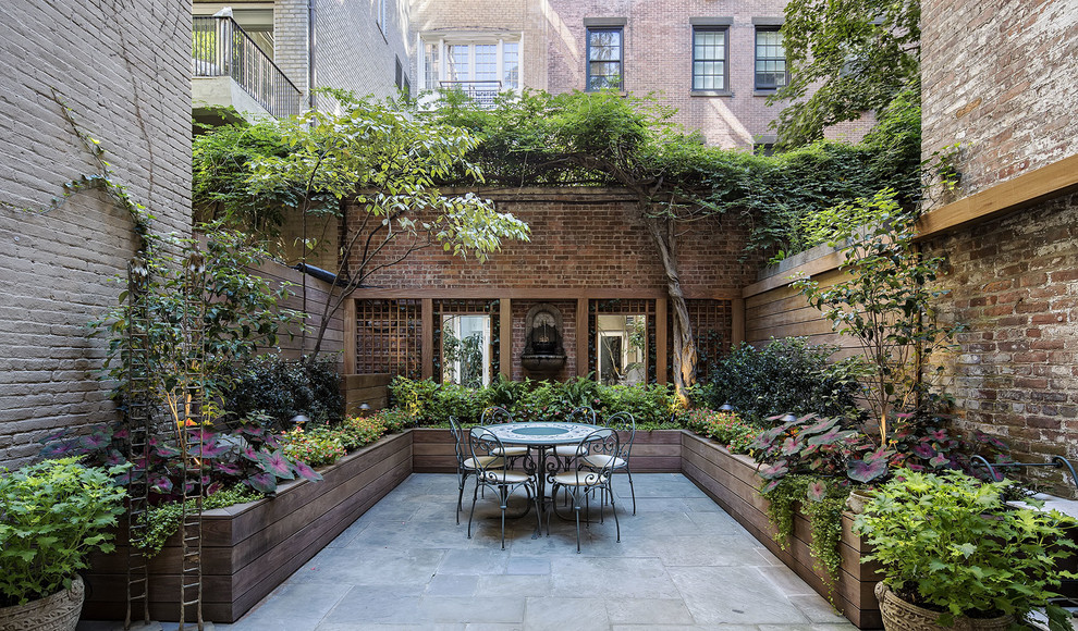 Example of a large classic backyard stone patio container garden design in New York with no cover