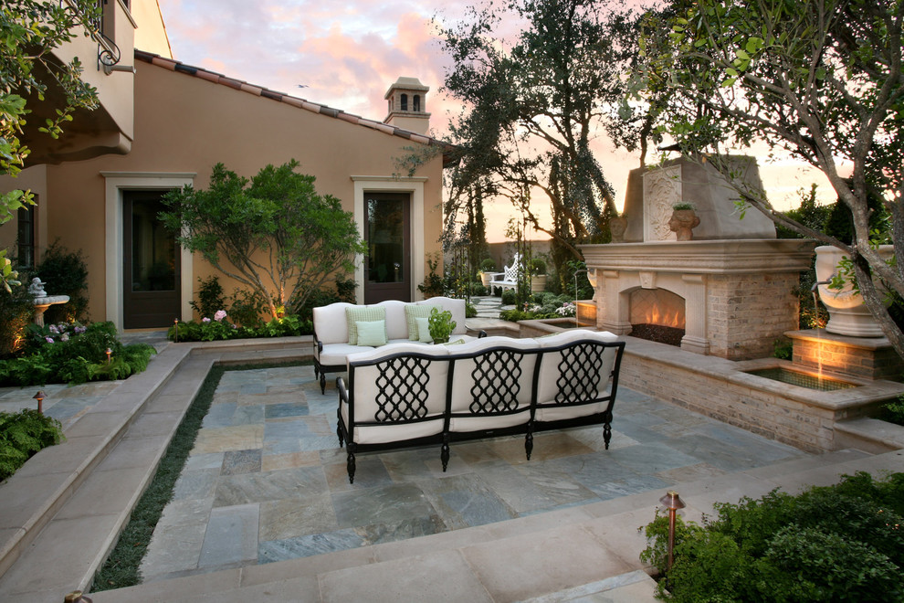 Mid-sized tuscan backyard patio photo in Orange County with a fire pit