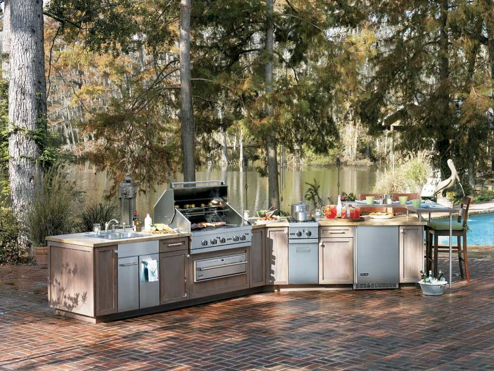 Example of a large classic backyard brick patio kitchen design in Other