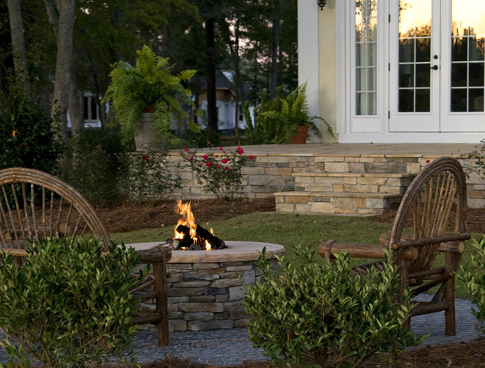 Example of a tuscan patio design in Raleigh with a fire pit