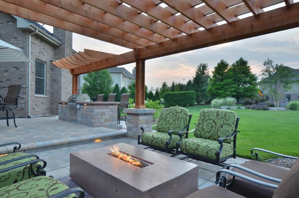 Mid-sized elegant backyard concrete paver patio kitchen photo in Chicago with a pergola