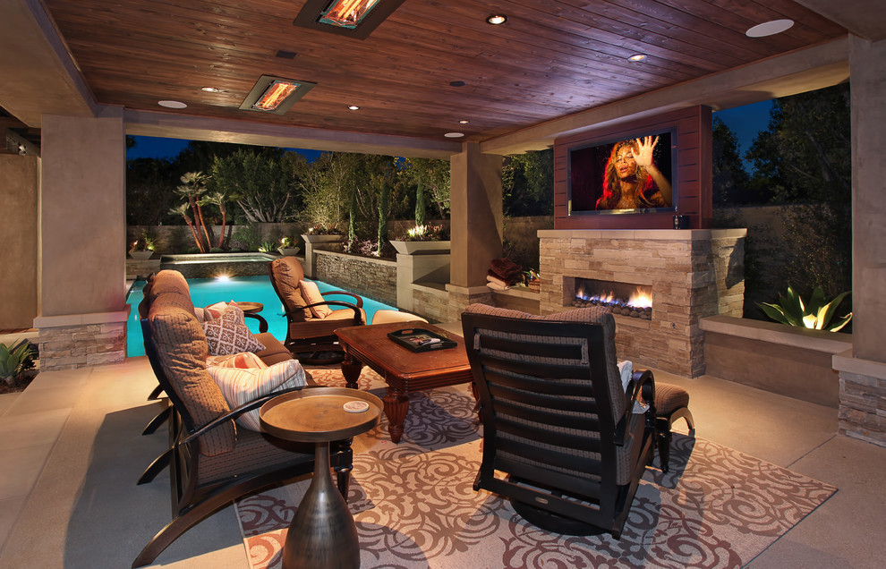 Patio - large contemporary backyard concrete paver patio idea in Orange County with a fire pit and a roof extension